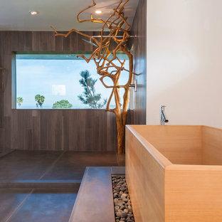 Asiatisk inredning av ett mycket stort en-suite badrum, med ett japanskt badkar, en öppen dusch, grå kakel, cementkakel, vita väggar, betonggolv, grått golv, med dusch som är öppen, släta luckor, svarta skåp, en toalettstol med hel cisternkåpa, ett avlångt handfat och träbänkskiva