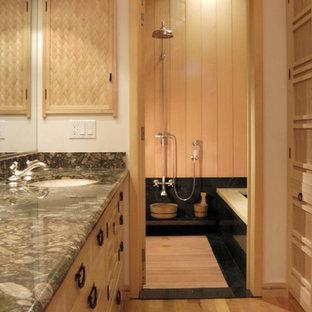 Diseño de cuarto de baño principal, asiático, pequeño, con puertas de armario de madera clara, encimera de granito, ducha abierta, paredes blancas, suelo de madera en tonos medios y bañera encastrada