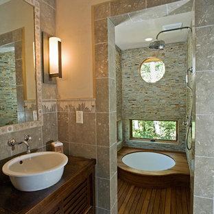 Modelo de cuarto de baño principal, rústico, pequeño, con lavabo sobreencimera, armarios con paneles lisos, puertas de armario de madera oscura, encimera de madera, bañera japonesa, ducha a ras de suelo, sanitario de una pieza, baldosas y/o azulejos de piedra, paredes verdes, suelo de piedra caliza y baldosas y/o azulejos grises