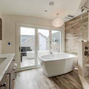 Mittelgroßes Modernes Badezimmer mit flächenbündigen Schrankfronten, freistehender Badewanne, Eckdusche, Porzellan-Bodenfliesen, Unterbauwaschbecken, braunem Boden, Falttür-Duschabtrennung, dunklen Holzschränken, beigefarbenen Fliesen, Kieselfliesen und beiger Wandfarbe in San Francisco