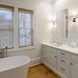 チャールストンの大きいビーチスタイルのおしゃれなマスターバスルーム (フラットパネル扉のキャビネット、白いキャビネット、置き型浴槽、アルコーブ型シャワー、白いタイル、大理石タイル、白い壁、無垢フローリング、アンダーカウンター洗面器、珪岩の洗面台、茶色い床、開き戸のシャワー、白い洗面カウンター) の写真