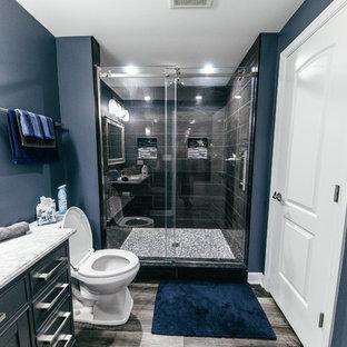 Diseño de cuarto de baño con ducha, minimalista, de tamaño medio, con armarios estilo shaker, puertas de armario grises, ducha empotrada, sanitario de una pieza, baldosas y/o azulejos grises, baldosas y/o azulejos de porcelana, paredes azules, suelo laminado, lavabo bajoencimera, encimera de cuarzo compacto, suelo gris, ducha con puerta corredera y encimeras blancas
