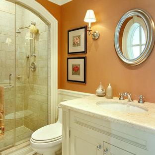 На фото: ванная комната среднего размера в классическом стиле с каменной плиткой, оранжевыми стенами, белыми фасадами, душем в нише, унитазом-моноблоком, полом из керамогранита, душевой кабиной, врезной раковиной, мраморной столешницей и фасадами с утопленной филенкой с