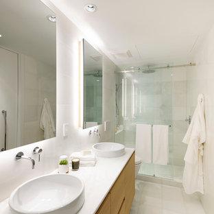 Immagine di una stanza da bagno padronale minimalista di medie dimensioni con ante lisce, ante in legno chiaro, piastrelle bianche, lastra di pietra, lavabo a bacinella, top in marmo, doccia alcova, WC a due pezzi, pareti bianche, pavimento in marmo e vasca da incasso