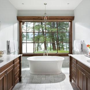 Inredning av ett klassiskt stort vit vitt en-suite badrum, med skåp i mörkt trä, ett fristående badkar, grå kakel, marmorkakel, vita väggar, marmorgolv, ett undermonterad handfat, bänkskiva i kvartsit, grått golv och luckor med infälld panel