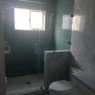 Foto di una stanza da bagno design di medie dimensioni con ante in stile shaker, ante bianche, doccia alcova, WC a due pezzi, piastrelle blu, piastrelle di vetro, pareti grigie, pavimento in marmo, top in marmo, pavimento grigio e porta doccia a battente