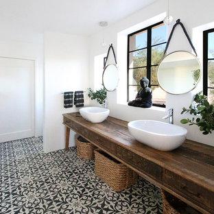 Неиссякаемый источник вдохновения для домашнего уюта: ванная комната в стиле кантри с искусственно-состаренными фасадами, белыми стенами, настольной раковиной, столешницей из дерева, разноцветным полом и коричневой столешницей
