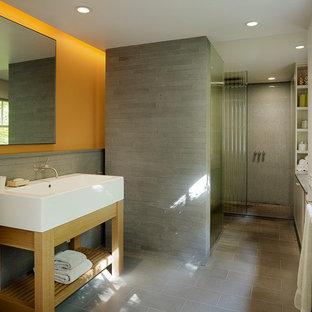 Modelo de cuarto de baño actual con lavabo de seno grande, armarios abiertos, puertas de armario de madera clara, ducha a ras de suelo, baldosas y/o azulejos grises y parades naranjas