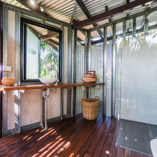 Photo of a tropical bathroom in Darwin with a corner shower, gray tile, dark hardwood floors, a vessel sink, wood benchtops, brown floor, an open shower, brown benchtops and a single vanity.