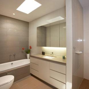 Cette image montre une douche en alcôve design de taille moyenne pour enfant avec un placard à porte plane, des portes de placard beiges, une baignoire posée, un WC suspendu, un carrelage marron, des carreaux de céramique, un sol en carrelage de porcelaine, un lavabo encastré, un plan de toilette en quartz modifié, un sol marron, une cabine de douche à porte battante, un plan de toilette beige, meuble simple vasque, meuble-lavabo encastré et un plafond à caissons.
