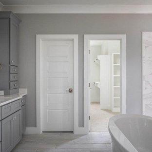 Imagen de cuarto de baño principal y casetón, clásico, de tamaño medio, con armarios con rebordes decorativos, puertas de armario grises, bañera exenta, ducha abierta, baldosas y/o azulejos blancos, paredes grises, lavabo integrado, suelo gris, ducha abierta y encimeras blancas
