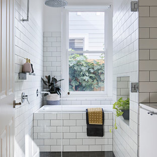 Contemporary 3/4 wet room bathroom in Geelong with flat-panel cabinets, white cabinets, a drop-in tub, white tile, subway tile, white walls, black floor and a hinged shower door.