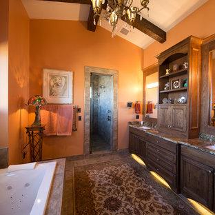 Immagine di una grande stanza da bagno padronale stile rurale con ante con bugna sagomata, ante in legno bruno, vasca da incasso, pareti arancioni, pavimento con piastrelle in ceramica, lavabo sottopiano, top in granito, pavimento beige, porta doccia a battente e top verde