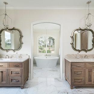 Diseño de cuarto de baño principal, clásico renovado, con armarios con paneles empotrados, puertas de armario de madera oscura, bañera exenta, paredes beige, lavabo bajoencimera, suelo blanco y encimeras beige