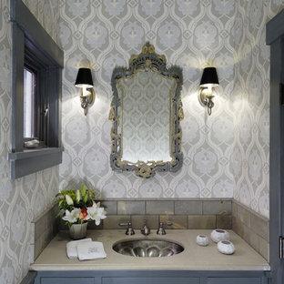 Immagine di una stanza da bagno contemporanea con lavabo sottopiano, ante blu e pareti multicolore