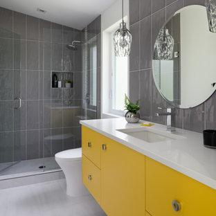 Aménagement d'une salle de bain contemporaine avec un placard à porte plane, des portes de placard jaunes, un carrelage gris, un lavabo encastré, un sol gris, une cabine de douche à porte battante, un plan de toilette blanc, meuble simple vasque, meuble-lavabo suspendu et un plafond voûté.