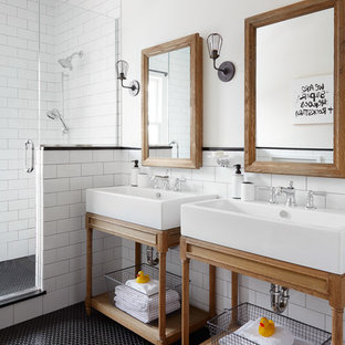 Example of a danish master black tile, white tile and subway tile mosaic tile floor and black floor corner shower design in Chicago with white walls, a console sink and a hinged shower door