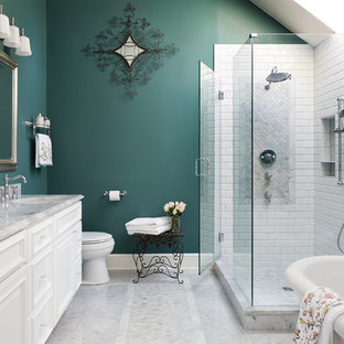 This is an example of a mid-sized traditional master bathroom in DC Metro with raised-panel cabinets, white cabinets, a freestanding tub, a corner shower, a one-piece toilet, white tile, ceramic tile, green walls, marble floors, an undermount sink, marble benchtops, grey floor, a hinged shower door and grey benchtops.