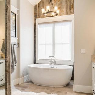 Inredning av ett rustikt en-suite badrum, med luckor med infälld panel, beige skåp, ett fristående badkar, grå väggar och beiget golv