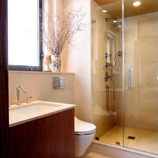 Example of a mid-sized minimalist alcove shower design in New York with flat-panel cabinets, dark wood cabinets, a wall-mount toilet, white walls, an undermount sink and quartzite countertops