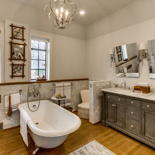 Elegant medium tone wood floor and brown floor claw-foot bathtub photo in Other with shaker cabinets, gray cabinets, white walls, an undermount sink and white countertops
