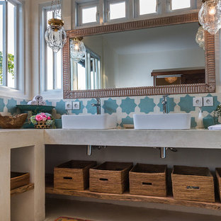 Imagen de cuarto de baño principal, bohemio, pequeño, con lavabo sobreencimera, armarios abiertos, encimera de cemento, ducha esquinera, sanitario de dos piezas, baldosas y/o azulejos beige, baldosas y/o azulejos de porcelana, paredes blancas y suelo de baldosas de porcelana
