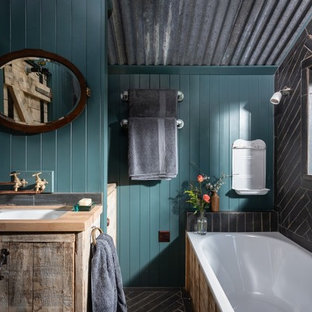 コーンウォールの中サイズのラスティックスタイルのおしゃれな子供用バスルーム (フラットパネル扉のキャビネット、淡色木目調キャビネット、ドロップイン型浴槽、青いタイル、青い壁、磁器タイルの床、オーバーカウンターシンク、木製洗面台、青い床、ベージュのカウンター) の写真