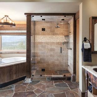На фото: ванная комната в стиле рустика с накладной раковиной, открытыми фасадами, искусственно-состаренными фасадами, душем в нише, бежевой плиткой, каменной плиткой, бежевыми стенами и накладной ванной с