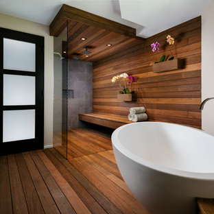 Large trendy master dark wood floor and brown floor bathroom photo in Miami with beige walls, a vessel sink and wood countertops