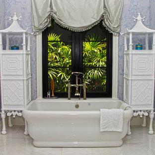 Immagine di una stanza da bagno padronale etnica con ante bianche, vasca freestanding, WC monopezzo, piastrelle bianche, pareti blu e pavimento in marmo