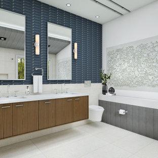 シカゴの大きいおしゃれなマスターバスルーム (フラットパネル扉のキャビネット、茶色いキャビネット、置き型浴槽、シャワー付き浴槽、壁掛け式トイレ、白いタイル、磁器タイル、白い壁、磁器タイルの床、横長型シンク、珪岩の洗面台、白い床、開き戸のシャワー、青い洗面カウンター) の写真