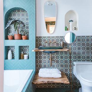 Foto di una stanza da bagno mediterranea con vasca/doccia, piastrelle verdi, piastrelle in ceramica, pareti bianche, pavimento con piastrelle in ceramica, lavabo a colonna, top in legno, pavimento verde e doccia aperta