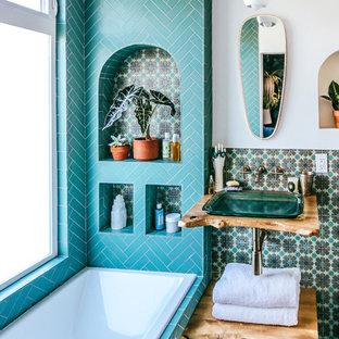 Modelo de cuarto de baño principal, mediterráneo, con baldosas y/o azulejos de cerámica, paredes blancas, suelo de baldosas de cerámica, encimera de madera, armarios abiertos, puertas de armario de madera oscura, bañera encastrada, baldosas y/o azulejos azules, lavabo suspendido, suelo azul y encimeras marrones