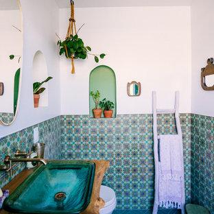 Modelo de cuarto de baño mediterráneo con combinación de ducha y bañera, baldosas y/o azulejos verdes, baldosas y/o azulejos de cerámica, paredes blancas, suelo de baldosas de cerámica, lavabo con pedestal, encimera de madera, suelo verde y ducha abierta