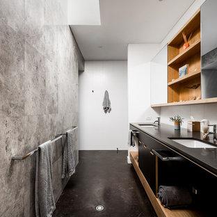 Ejemplo de cuarto de baño principal, minimalista, con armarios con paneles lisos, puertas de armario negras, paredes blancas, suelo de cemento, lavabo bajoencimera, suelo negro y encimeras negras