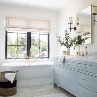 Idéer för maritima vitt en-suite badrum, med möbel-liknande, blå skåp, ett fristående badkar, vita väggar, ett undermonterad handfat och grått golv