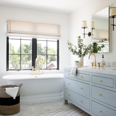 Beach style master gray floor and double-sink freestanding bathtub photo in San Francisco with furniture-like cabinets, blue cabinets, white walls, an undermount sink, white countertops and a freestanding vanity