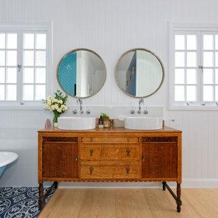ブリスベンのトロピカルスタイルのおしゃれな浴室 (フラットパネル扉のキャビネット、中間色木目調キャビネット、猫足バスタブ、グレーのタイル、白い壁、淡色無垢フローリング、ベッセル式洗面器、木製洗面台、ベージュの床、ブラウンの洗面カウンター、洗面台2つ、独立型洗面台、塗装板張りの壁) の写真