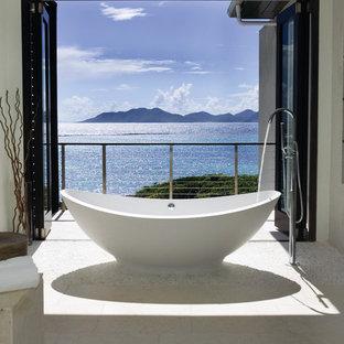 他の地域の広いトロピカルスタイルのおしゃれなマスターバスルーム (置き型浴槽、ベージュのタイル、白い壁、玉石タイル) の写真