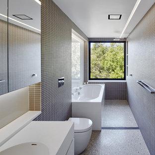 Cette image montre une salle d'eau design de taille moyenne avec un placard à porte vitrée, un WC suspendu, un carrelage gris, des carreaux de céramique, un mur gris, béton au sol, un lavabo intégré, des portes de placard blanches, une baignoire encastrée et un plan de toilette en quartz modifié.