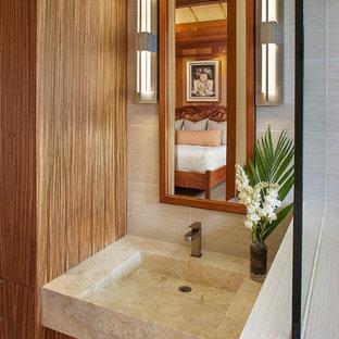 Ispirazione per una stanza da bagno tropicale di medie dimensioni con ante lisce, ante in legno scuro, pareti beige e lavabo integrato