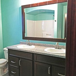 他の地域の中くらいのトラディショナルスタイルのおしゃれな浴室 (落し込みパネル扉のキャビネット、濃色木目調キャビネット、分離型トイレ、青い壁、クッションフロア、オーバーカウンターシンク、御影石の洗面台) の写真