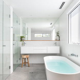 Inspiration for a mid-sized contemporary master bathroom in Perth with furniture-like cabinets, white cabinets, a freestanding tub, white tile, ceramic tile, white walls, porcelain floors, an integrated sink, grey floor, white benchtops, a curbless shower and a hinged shower door.