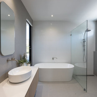 This is an example of a contemporary bathroom in Perth with light wood cabinets, a freestanding tub, an open shower, gray tile, porcelain tile, tile benchtops, white benchtops, a double vanity and a floating vanity.
