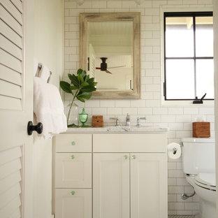 Diseño de cuarto de baño con ducha, marinero, pequeño, con armarios estilo shaker, puertas de armario blancas, encimera de mármol, baldosas y/o azulejos blancos, baldosas y/o azulejos de cemento, lavabo bajoencimera, sanitario de dos piezas, paredes blancas y suelo con mosaicos de baldosas