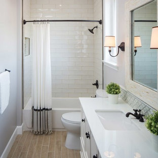 Large traditional bathroom in Los Angeles with a submerged sink, white cabinets, stone tiles, grey walls, an alcove bath, white tiles, a shower/bath combination and recessed-panel cabinets.