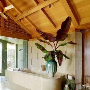 Foto di una stanza da bagno padronale tropicale con vasca ad angolo, doccia doppia, pareti beige e pavimento beige
