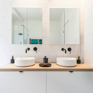 This is an example of a contemporary bathroom in Melbourne with flat-panel cabinets, white cabinets, a drop-in tub, white tile, a vessel sink, wood benchtops, brown benchtops and a double vanity.