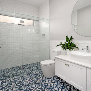 Mid-sized beach style kids bathroom in Brisbane with shaker cabinets, white cabinets, an open shower, a two-piece toilet, white tile, ceramic tile, grey walls, ceramic floors, a vessel sink, engineered quartz benchtops, blue floor, a hinged shower door, white benchtops, a niche, a single vanity and a floating vanity.