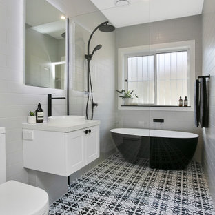 Design ideas for a mid-sized transitional wet room bathroom in Sydney with white cabinets, gray tile, porcelain tile, white walls, porcelain floors, a vessel sink, engineered quartz benchtops, an open shower, white benchtops, a freestanding tub, a two-piece toilet and multi-coloured floor.